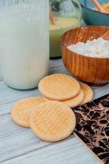 Vista lateral de biscoitos com cereais de leite condensado de queijo cottage de leite na superfície de madeira