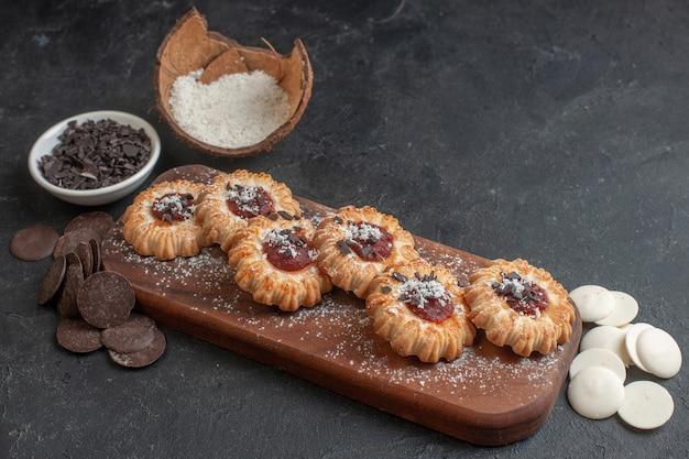Vista lateral de biscoitos com impressão digital recheados de geleia recém-assados em uma bandeja de madeira e vários chocolates na superfície escura