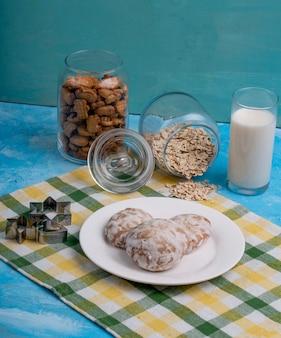 Vista lateral de biscoitos de gengibre em um prato branco na mesa da cozinha
