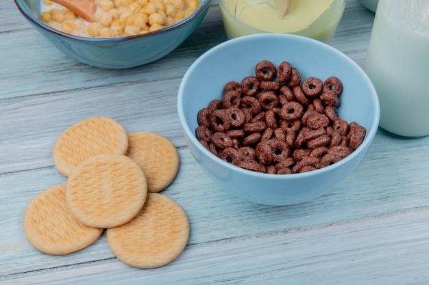 Vista lateral de biscoitos e cereais em uma tigela com café da manhã cereais leite condensado leite na mesa de madeira
