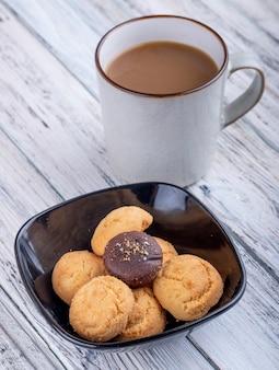 Vista lateral de biscoitos em uma tigela preta e um copo com cacau na madeira