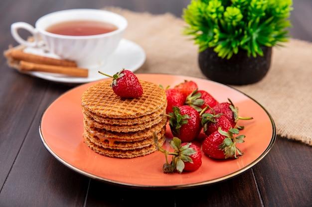 Vista lateral de biscoitos waffle e morangos no prato e xícara de chá com canela no pires e flores no saco e madeira