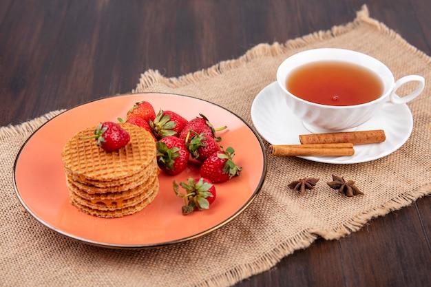Vista lateral de biscoitos waffle e morangos no prato e xícara de chá com canela no pires em pano de saco e madeira