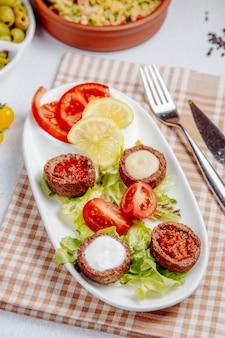Vista lateral de bolas fritas com cogumelos e tomates na mesa