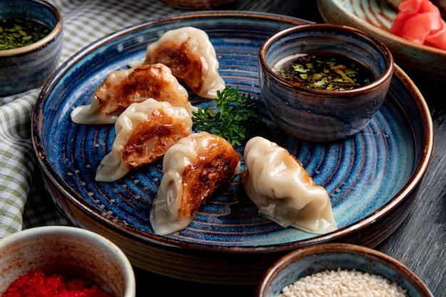 Vista lateral de bolinhos asiáticos tradicionais com carne e legumes, servidos com molho de soja em um prato rústico