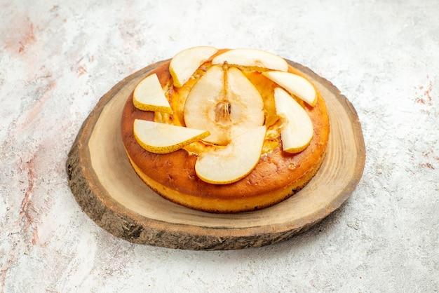 Vista lateral de bolo apetitoso bolo de pêra apetitoso na placa de madeira na superfície branca