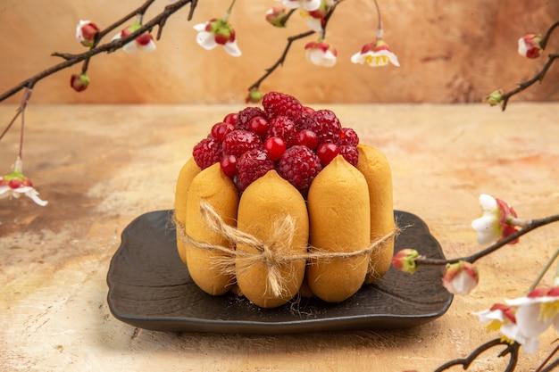 Vista lateral de bolo de presente recém-assado com frutas na mesa de cores misturadas