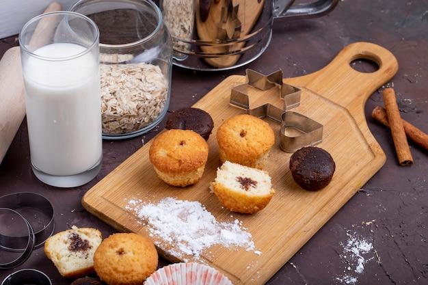 Vista lateral de bolos com chocolate em uma tábua de madeira