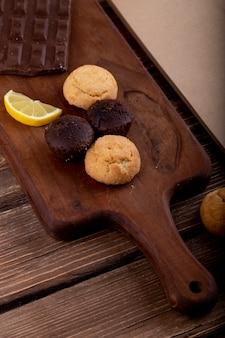Vista lateral de bolos com fatia de limão e chocolate escuro sobre uma tábua de madeira
