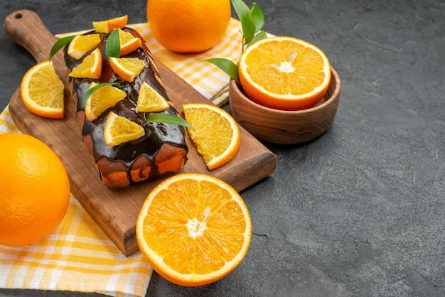 Vista lateral de bolos moles inteiros e laranjas cortadas com folhas na mesa escura