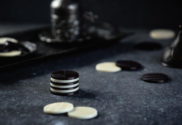 Vista lateral de bombons de chocolate preto e branco na parede escura