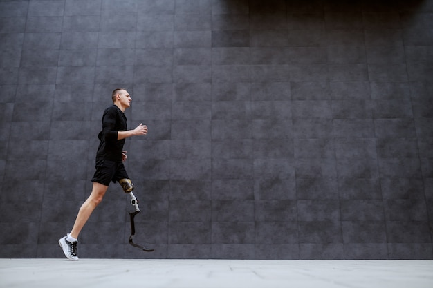 Vista lateral de bonito apto desportista caucasiano com perna artificial correndo do lado de fora.
