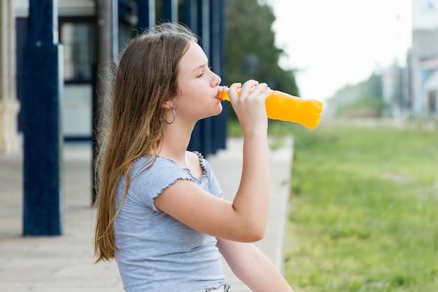 Vista lateral, de, bonito, menina adolescente, bebendo, suco, parque