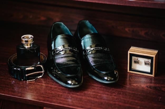 Vista lateral de botões de punho, cinto, sapatos, perfume.