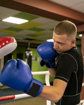 Vista lateral de boxeador masculino com treinador ao lado do ringue de boxe