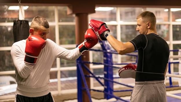 Vista lateral de boxeador praticando com treinador próximo ao ringue