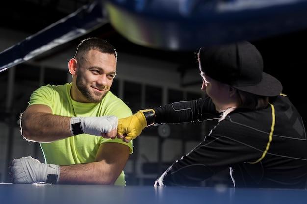 Vista lateral de boxers masculinos e femininos em uma colisão do punho
