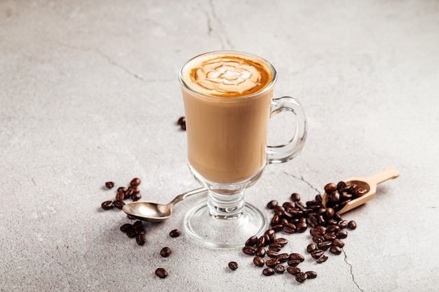 Vista lateral de café com leite decorado em uma caneca de vidro no fundo de concreto