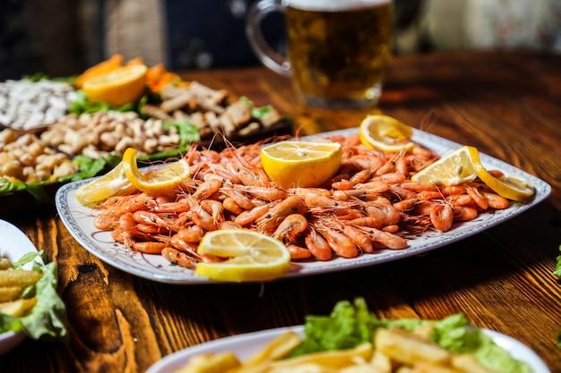 Vista lateral de camarão cozido com fatias de limão em um prato com lanches de cerveja e um copo de cerveja na mesa