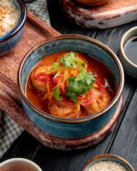 Vista lateral de camarão frito com legumes e molho picante em uma tigela na placa de madeira em rústico