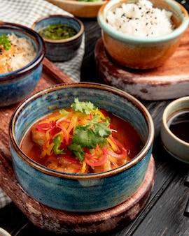 Vista lateral de camarão frito com legumes e molho picante em uma tigela no rústico