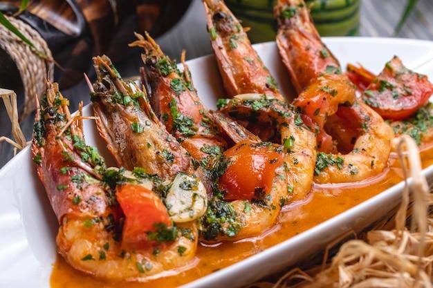 Vista lateral de camarão frito em molho com tomate e ervas