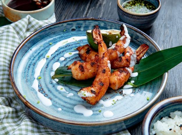 Vista lateral de camarão grelhado com molho num prato de madeira