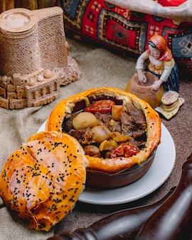 Vista lateral de carne assada com castanhas e frutas secas em uma panela com massa por cima, cozida no forno