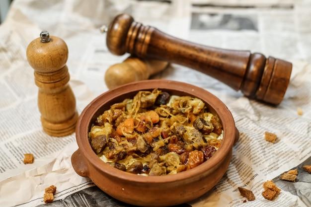 Vista lateral de carne assada em uma panela de barro com frutas secas cebolas e sal e pimenta no jornal