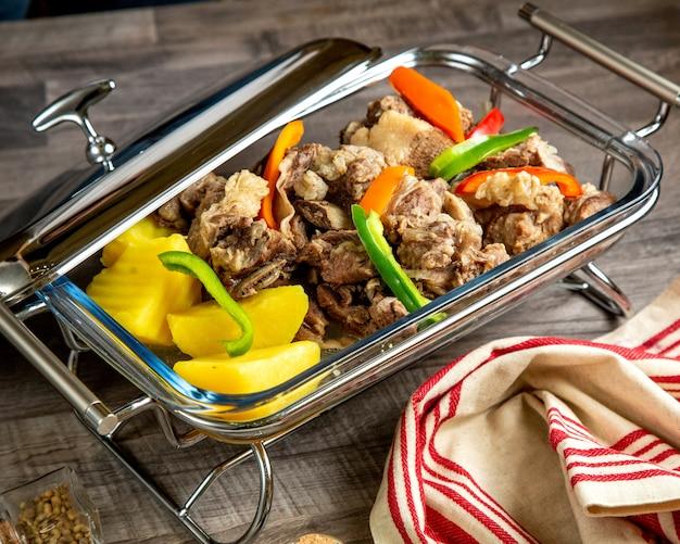 Vista lateral de carne cozida com batatas cozidas e legumes