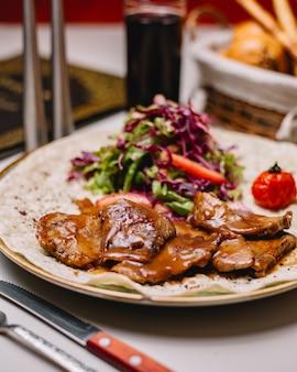 Vista lateral de carne de cordeiro grelhada com molho de alface repolho roxo e tomate na pita