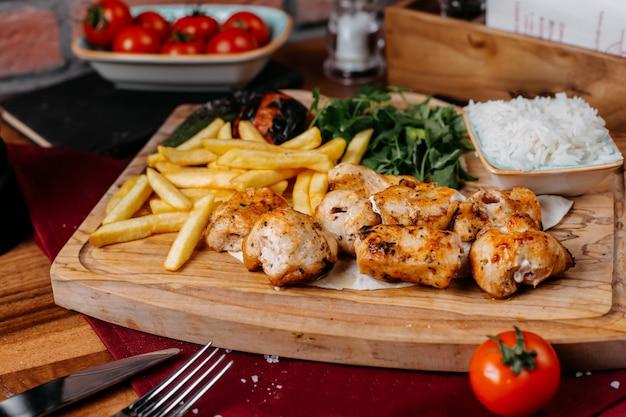 Vista lateral de carne de frango grelhado e legumes com batatas fritas e ervas em uma placa de madeira