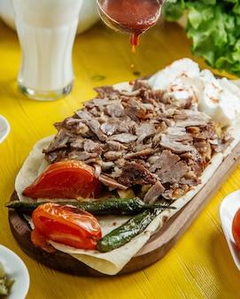 Vista lateral de carne doner kebab no prato com legumes grelhados