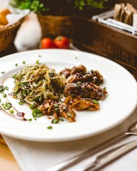 Vista lateral de carne frita em molho com repolho e cebola verde