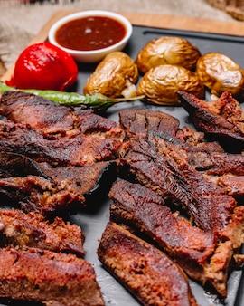 Vista lateral de carne grelhada com batatas e legumes grelhados com molhos