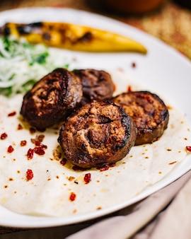 Vista lateral de carne grelhado no pão pita com cebola