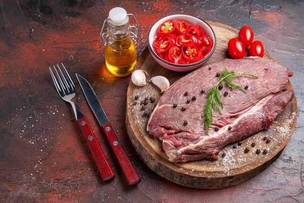 Vista lateral de carne vermelha em bandeja de madeira e alho verde e pimenta picada garfo e faca de garrafa de óleo caído em fundo escuro