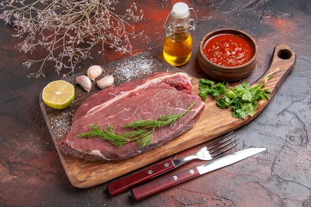Vista lateral de carne vermelha em uma tábua de madeira e ketchup de limão com garrafa de óleo verde de alho em fundo escuro