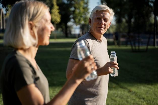 Vista lateral de casal bebendo água ao ar livre