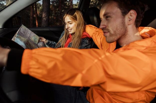 Vista lateral de casal com mapa dentro do carro em viagem