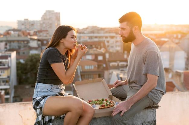 Vista lateral de casal comendo pizza ao ar livre