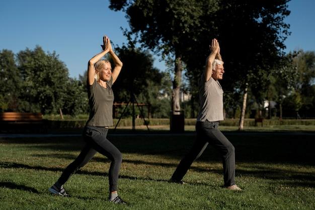 Vista lateral de casal de idosos fazendo ioga ao ar livre