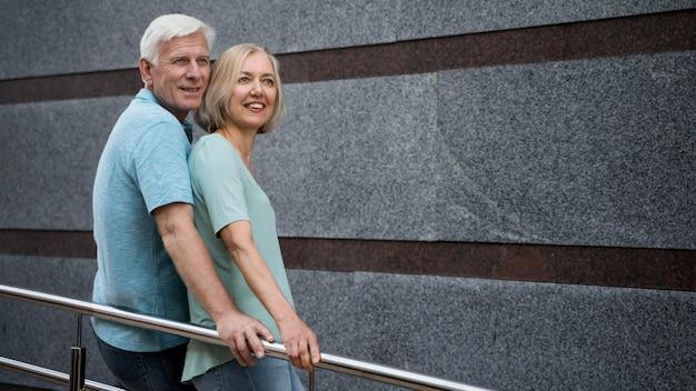 Vista lateral de casal de idosos posando juntos ao ar livre