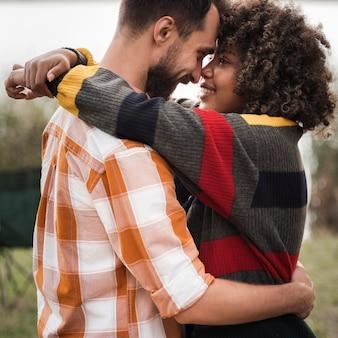 Vista lateral de casal feliz se abraçando ao ar livre