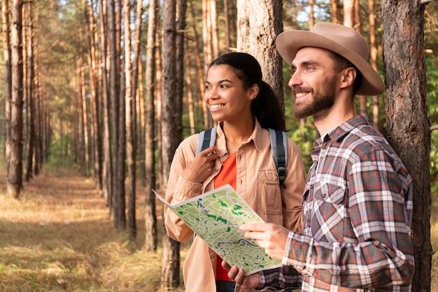 Vista lateral de casal olhando para longe na natureza com espaço de cópia