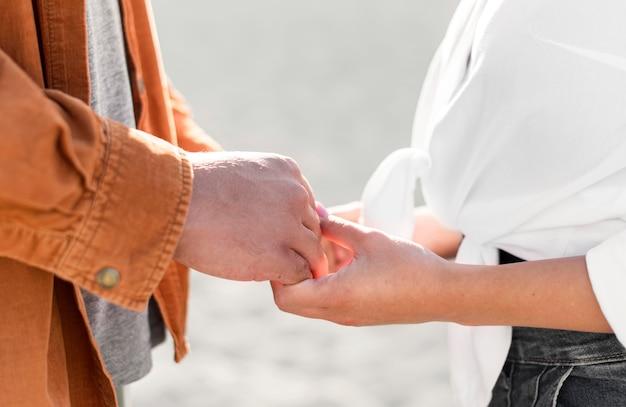 Vista lateral de casal romântico de mãos dadas ao ar livre