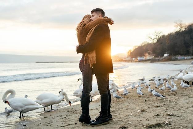 Vista lateral de casal se abraçando na praia no inverno