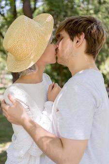 Vista lateral de casal se beijando ao ar livre
