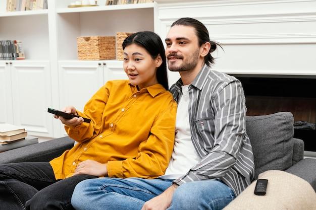 Vista lateral de casal sentado no sofá assistindo tv