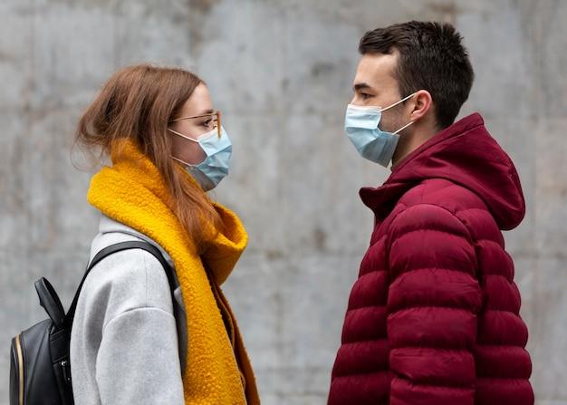 Vista lateral de casal usando máscaras médicas